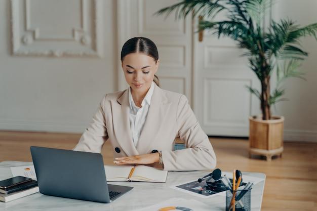 Портрет улыбающейся молодой кавказской деловой женщины в светло-бежевом официальном костюме с волосами, завязанными в хвост, сидящей за большим белым столом, работающей с ноутбуком и записывающей вещи с размытым фоном