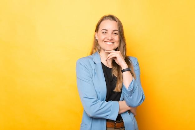 Портрет улыбающейся молодой веселой женщины в непринужденной обстановке, смотрящей в камеру на желтом фоне