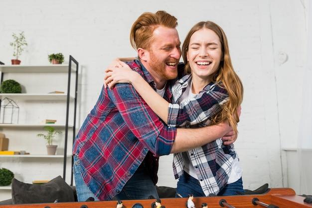 Портрет улыбающиеся молодые пары, обнимая друг друга после игры в футбол