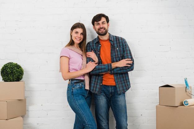 카메라를 찾고 흰 벽 앞에 서있는 젊은 부부 미소의 초상화