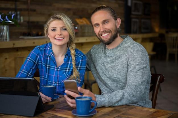 カフェでコーヒーとテクノロジーと笑顔の若いカップルの肖像画