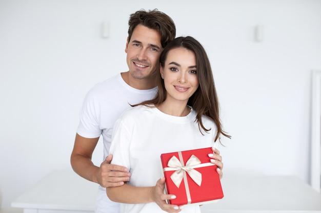 Портрет улыбающейся молодой пары с подарочной коробкой дома