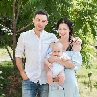 공원에서 자신의 아기와 함께 웃는 젊은 부부의 초상화