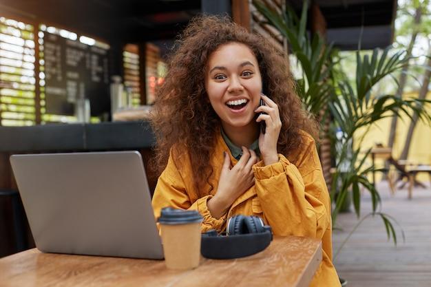 카페 테라스에서 siting 젊은 어두운 피부 곱슬 여자 미소의 초상화, 노트북에서 작동, 커피를 마시고, 웃고 친구와 전화로 이야기. 노란색 코트를 입고.