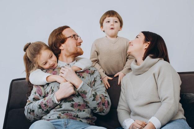 Портрет усмехаясь молодой семьи с маленькими детьми preschooler сидит на кресле в живущей комнате.