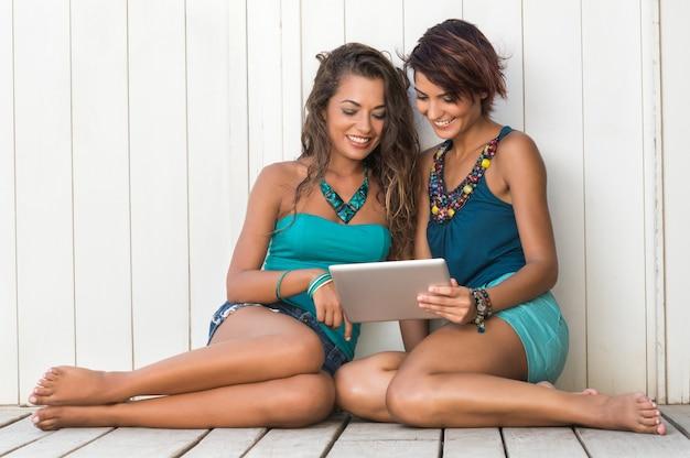 ビーチでデジタルタブレットを使用して笑顔の若い女性の友人の肖像画