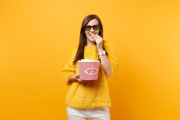 밝은 노란색 배경에 격리된 양동이에서 팝콘을 먹고 영화 영화를 보고 있는 3d 아이맥스 안경을 쓴 웃고 있는 어린 소녀의 초상화. 영화 라이프 스타일 개념에서 사람들은 진실한 감정. 공간을 복사합니다.