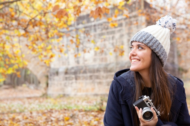 秋の風景の冬の服を着て笑顔の少女の肖像画。彼女は手にビンテージカメラを持っています。テキスト用のスペース。