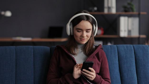 モバイルアプリケーションでお気に入りの音楽トラックを選択して、ヘッドフォンを身に着けている若い女の子の笑顔の肖像画