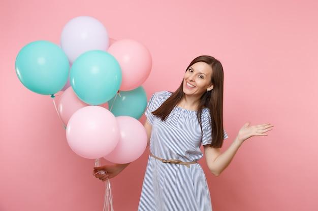 밝은 분홍색 배경에 격리된 복사 공간을 옆으로 가리키는 화려한 공기 풍선을 들고 파란 드레스를 입고 웃고 있는 젊은 행복한 여성의 초상화. 생일 휴일 파티 개념입니다.