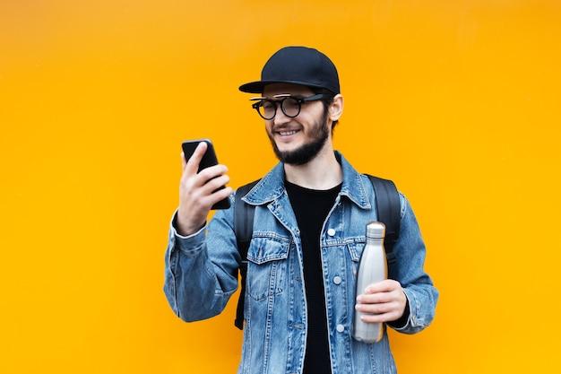 笑顔の若い流行に敏感な男の肖像画、水のための鋼のサーモエコボトルを保持し、オレンジ色のスマートフォンで見て