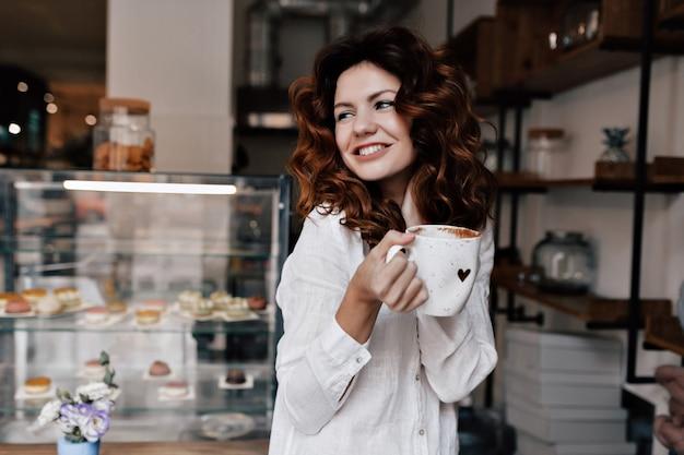 Портрет улыбающейся молодой леди с чашкой кофе, стоящей у прилавка и ожидающей клиентов