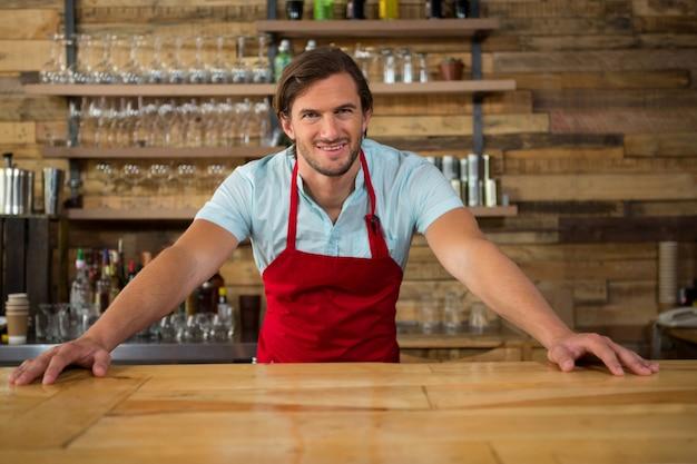 コーヒーショップのカウンターで笑顔の若い男性バリスタの肖像画