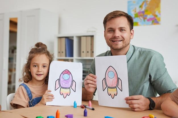 Портрет улыбающегося молодого человека и маленькой девочки, показывающих фотографии космических ракет во время урока рисования в дошкольном учреждении