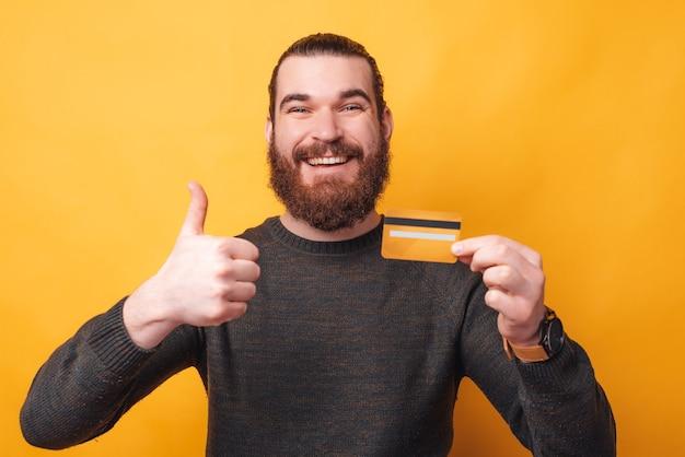 クレジットカードを持って親指を立てて笑顔の若い男の肖像画