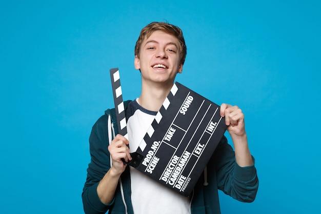 Портрет улыбающегося молодого человека в повседневной одежде держит классический черный фильм, делая с 'хлопушкой', изолированную на синей стене. концепция образа жизни искренние эмоции людей.