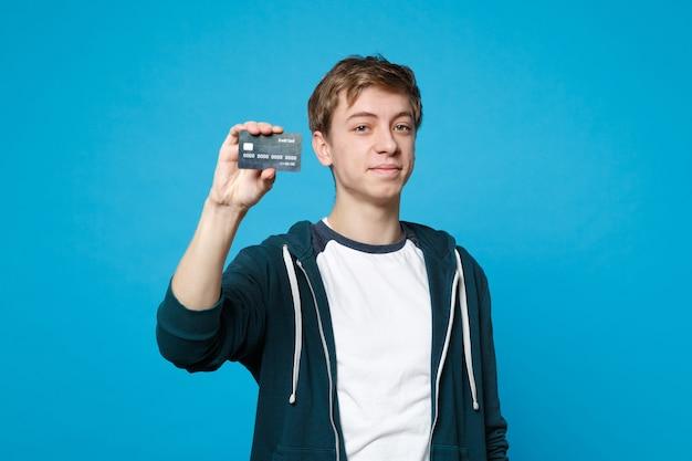 青い壁に分離されたクレジットカードを保持しているカジュアルな服を着て笑顔の若い男の肖像画。人々の誠実な感情、ライフスタイルのコンセプト。