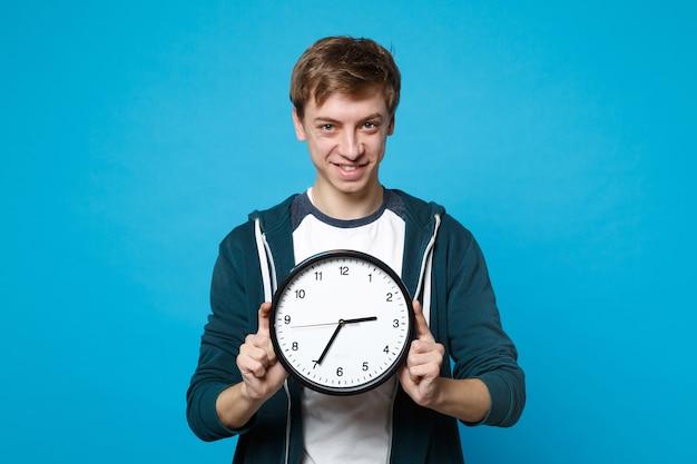 Портрет улыбающегося молодого человека в повседневной одежде, держащего круглые часы, изолированные на синей стене. время уходит. люди искренние эмоции, концепция образа жизни.