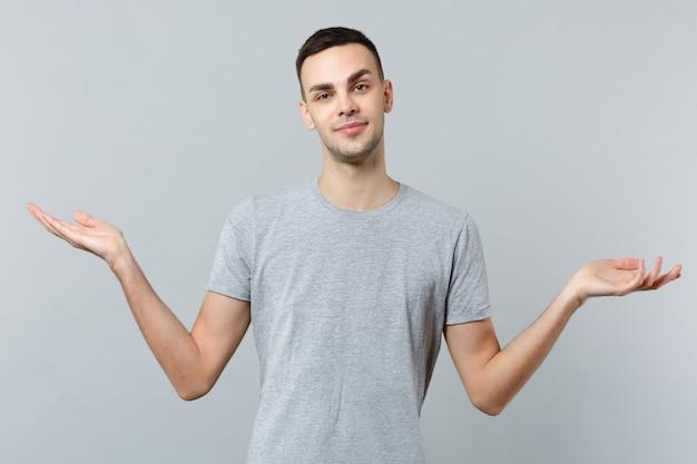 Портрет улыбающегося молодого человека в повседневной одежде, разводящего руками в сторону