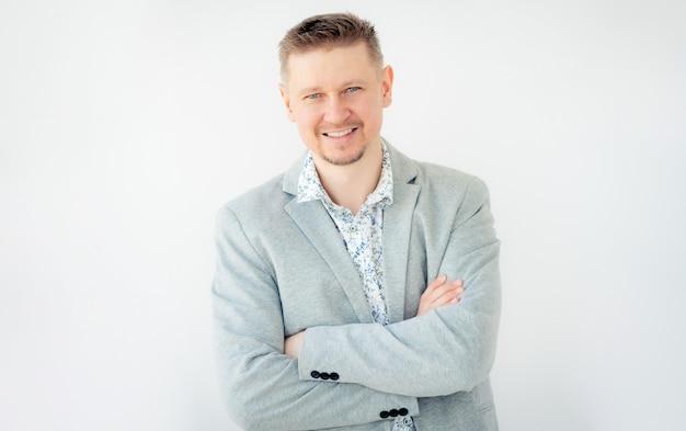 白い背景で隔離のグレーのジャケットを着た笑顔の若い男の肖像