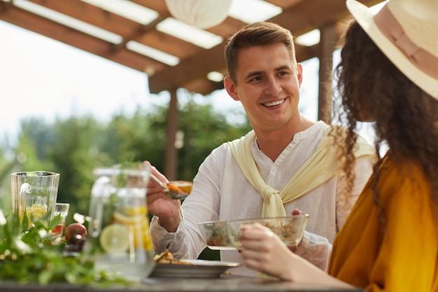 여름 파티에서 야외에서 친구 및 가족과 함께 저녁 식사를 즐기면서 여자 친구를보고 웃는 젊은 남자의 초상화