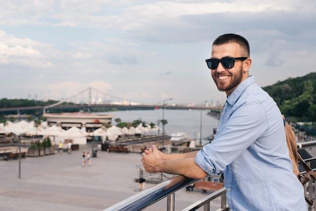 Портрет улыбающегося молодого человека, стоящего возле перил, глядя на камеру