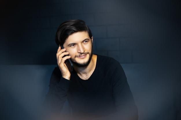 スマートフォンで話している笑顔の若い男の肖像画。ソファに座っています。黒レンガの壁の背景に。