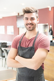 Portrait of smiling young man with apron standing in the bar