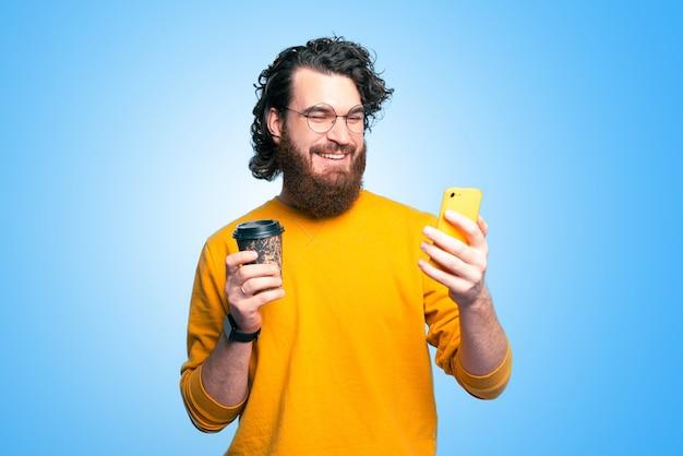スマートフォンを使用して、行くためにコーヒーのカップを保持しているひげと笑顔の若い男の肖像画