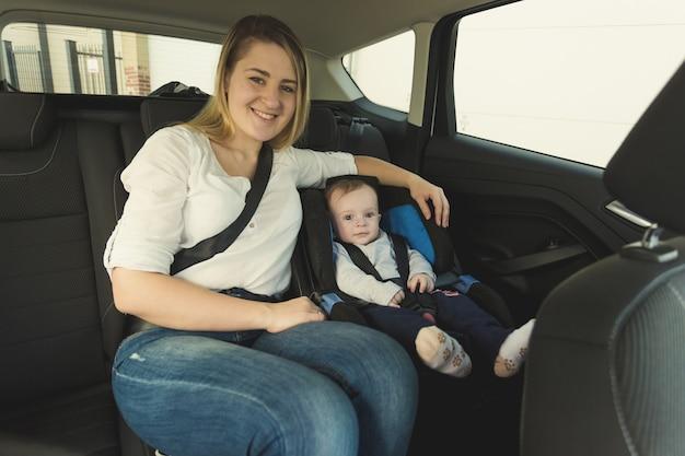 자동차 안전 좌석에 웃는 젊은 엄마와 아기의 초상화