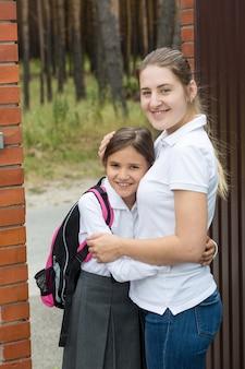 彼女を学校に見送る前に彼女の娘を抱き締める笑顔の若い母親の肖像画