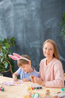 Портрет улыбающейся молодой матери, сидящей за столом и создающей красивую пасхальную открытку с сыном в ободке из кроличьих ушей