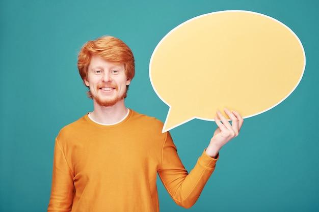 파란 벽에 배너처럼 보이는 웃고 있는 젊은 빨간 머리 블로거의 초상화