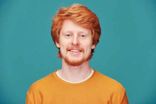 青でポーズをとって髪の頭全体と笑顔の若い赤毛の男の肖像画