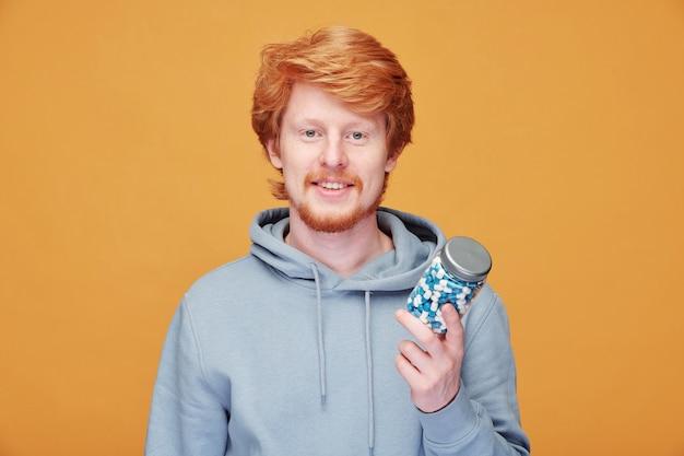 オレンジ色の健康のためにビタミンを服用しているパーカーの笑顔の若い赤毛の男の肖像画