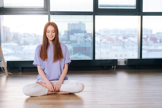 明るい事務室の窓の背景に蓮華座の床に座って瞑想する笑顔の若いリラックスした女性の肖像画。
