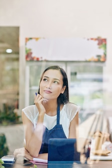 그녀의 사업 개발에 대한 꿈을 꾸고 웃는 젊은 베트남 카페 주인의 초상화