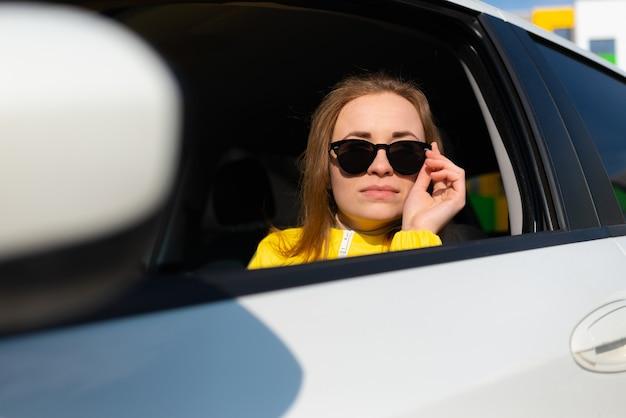 車に座っているサングラスを下げる黄色いジャケットを着た笑顔の若い女性のポートレート。