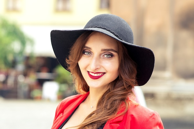 Портрет улыбающейся молодой женщины в черной шляпе l на открытом воздухе.