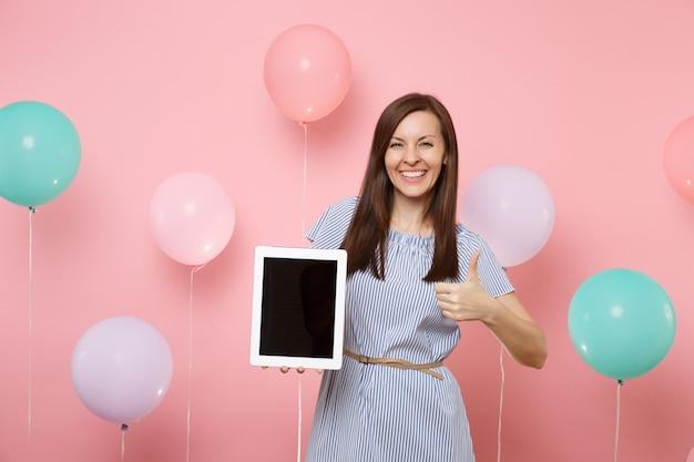 カラフルな空気風船とパステルピンクの背景に親指を示す空白の空の画面でタブレットpcコンピューターを保持している青いドレスで笑顔の若い女性の肖像画。誕生日の休日のパーティーのコンセプト。