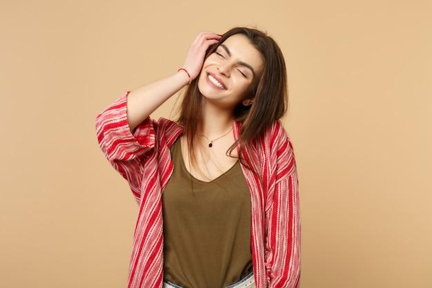 スタジオでパステルベージュの背景に隔離された顔に手を置いて目を閉じたままカジュアルな服を着た若い女性の笑顔の肖像画。人々の誠実な感情のライフスタイルの概念。コピースペースをモックアップします。