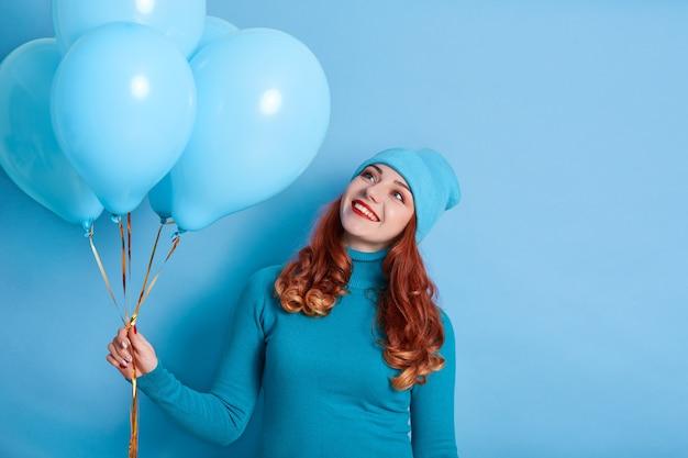 彼女の風船を脇に見てカジュアルな服を着て笑顔の若い女性の肖像画