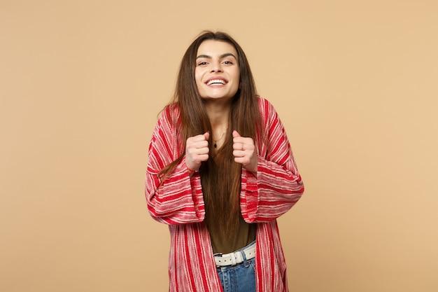 カメラを探しているカジュアルな服を着て、スタジオでパステルベージュの壁の背景に分離された拳を食いしばって笑顔の若い女性の肖像画。人々の誠実な感情、ライフスタイルのコンセプト。コピースペースをモックアップします。