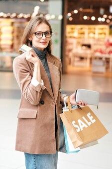 ショッピングバッグを持って立って、支払いにクレジットカードを使用して眼鏡をかけて笑顔の若い女性の肖像画