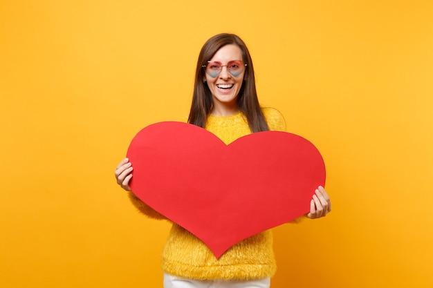 明るい黄色の背景で隔離空の空白の赤いハートを保持している毛皮のセーターとハートの眼鏡で笑顔の若い女性の肖像画。人々の誠実な感情、ライフスタイルのコンセプト。広告エリア。