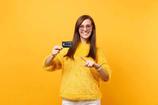 明るい黄色の背景で隔離のクレジットカードの人差し指を指している毛皮のセーターハート眼鏡で笑顔の若い女性の肖像画。人々の誠実な感情、ライフスタイルのコンセプト。広告エリア。