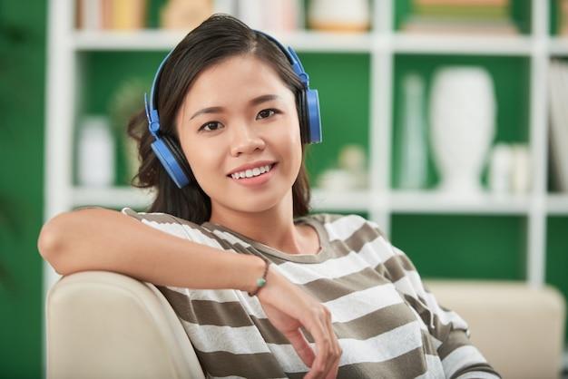 彼女の肘掛け椅子に寄りかかってカメラを見ているヘッドフォンで笑顔の若い女性の肖像画