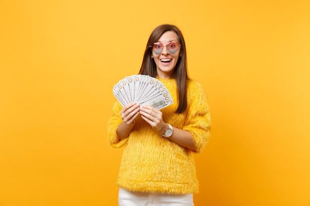 Портрет улыбающейся молодой женщины в сердечных очках, держащей пачку долларов, наличных денег, изолированных на ярко-желтом фоне. люди искренние эмоции, концепция образа жизни. рекламная площадка.