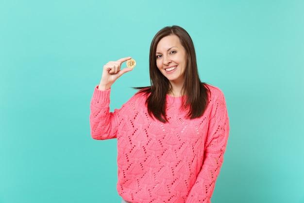 스튜디오의 파란색 청록색 벽 배경에 격리된 미래 통화인 비트코인을 손에 들고 있는 분홍색 스웨터를 입은 웃고 있는 젊은 여성의 초상화. 사람들이 라이프 스타일 개념입니다. 복사 공간을 비웃습니다.