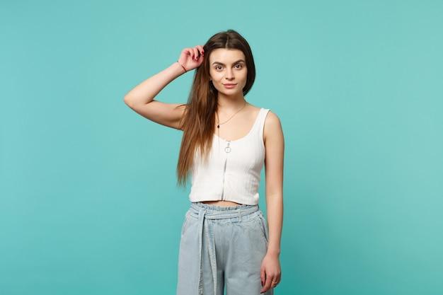 푸른 청록색 벽 배경에 격리된 머리에 손을 얹고 카메라를 바라보는 가벼운 캐주얼 옷을 입고 웃고 있는 젊은 여성의 초상화. 사람들은 진심 어린 감정, 라이프 스타일 개념입니다. 복사 공간을 비웃습니다.